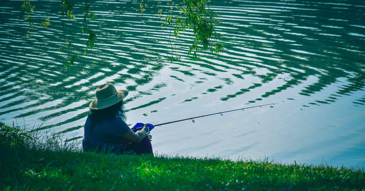 A person that is sitting in the grass near water