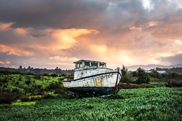 A boat sitting on top of a grass covered field